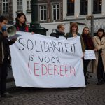 """[Group of people holding a banner with the slogan """"Solidariteit is voor iedereen""""]"""